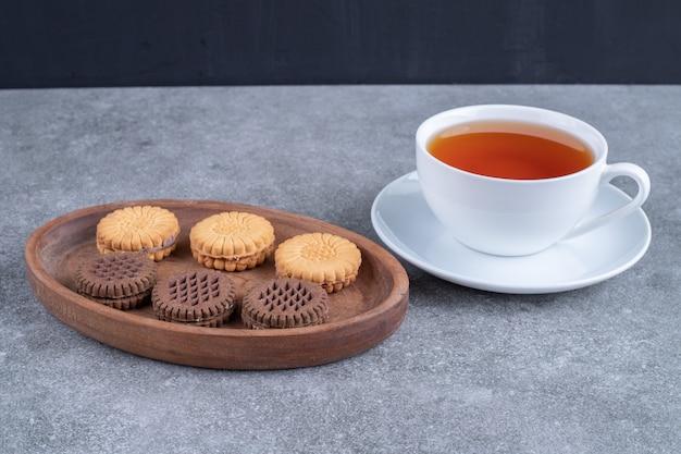 Herbatniki owsiane i kakaowe z filiżanką herbaty na marmurowej powierzchni