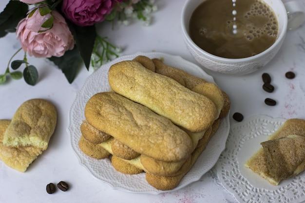 Herbatniki savoyardi, kawa i kwiaty na białej marmurowej powierzchni