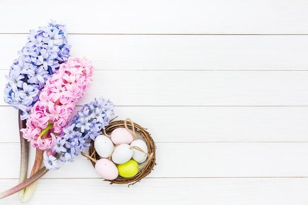 Hiacyntowe kwiaty i ozdobne pisanki w małym gnieździe na białym stole. widok z góry, miejsce na kopię