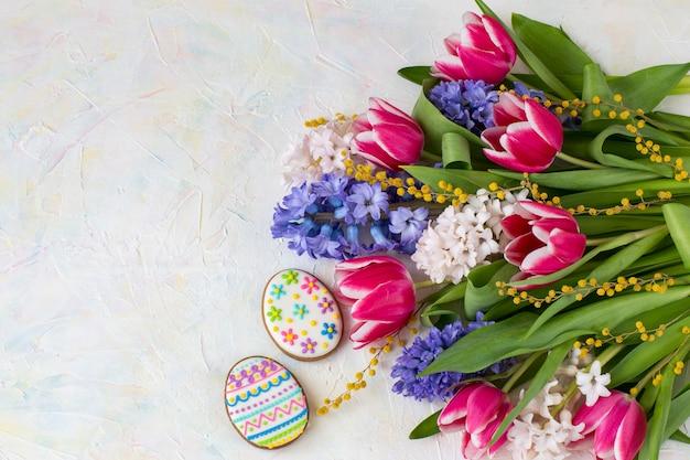 Hiacynty, tulipany, mimoza i dwa ciasta w kształcie wielkanocnych jaj