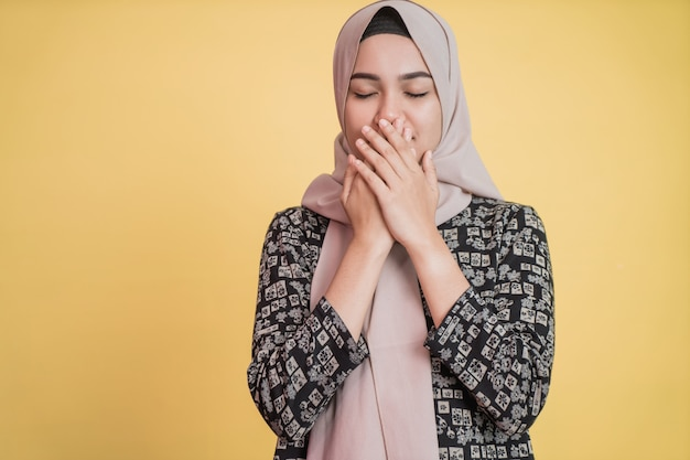 Hidżab dziewczyna zakrywa usta obiema rękami i zamkniętymi oczami