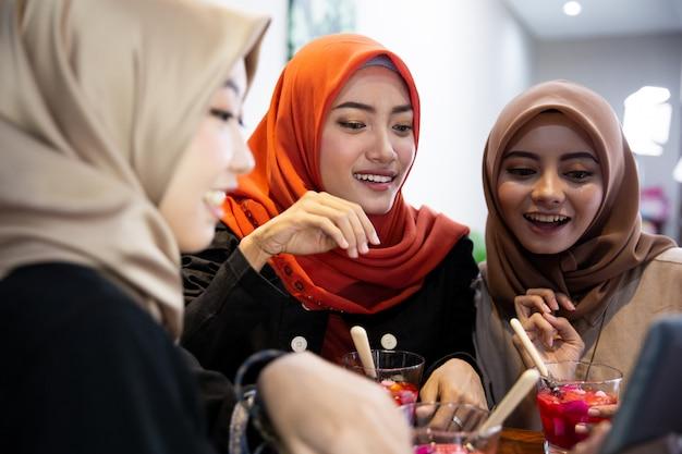 Hidżab kobiety i przyjaciele za pomocą cyfrowego tabletu czekają, przerywając swój post