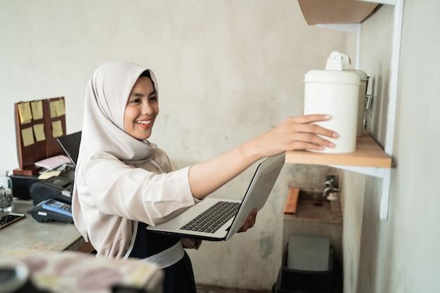 Hidżab właściciel kawiarni kobiety używają laptopa