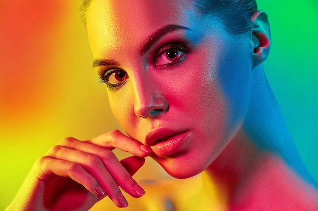 High fashion model kobieta w kolorowe jasne światła pozowanie w studio, portret pięknej seksownej dziewczyny z modnym makijażem i manicure. projekt artystyczny, kolorowy makijaż. na kolorowym żywym tle.