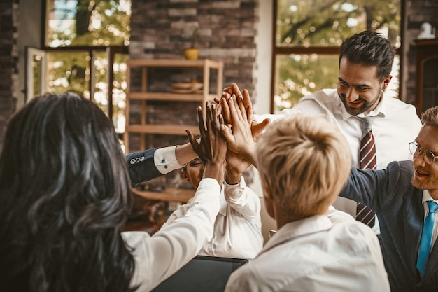 High five gest of diverse business team in office