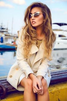 Hight fashion portret pięknej modelki z modnymi ombre włosami, przytulnym jesiennym płaszczem z kremowej wełny, złotą bluzką i okularami przeciwsłonecznymi, niesamowitym portem i klubem jachtowym.