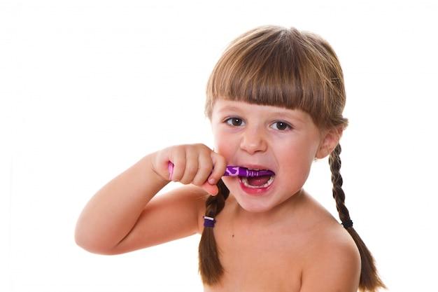 Higiena dentystyczna. szczęśliwa dziewczynka szczotkuje zęby