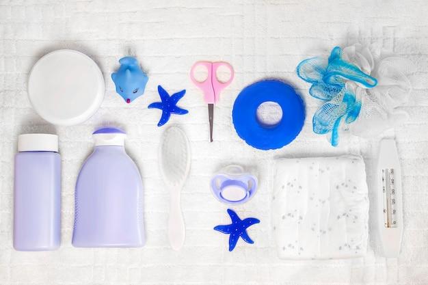 Higiena dziecięca: artykuły do kąpieli, butelka szamponu, gumowa zabawka, gąbka, grzebień, termometr, nożyczki bezpieczeństwa widok z góry, na białym tle. miejsce na kopię. zestaw do higieny osobistej dla dzieci. akcesoria do kąpieli.