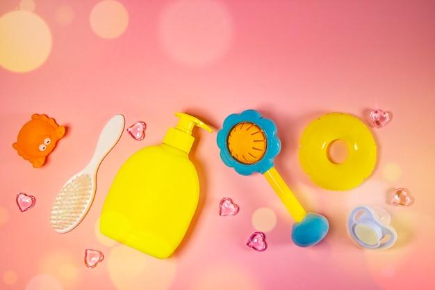 Higiena dziecięca: artykuły do kąpieli, butelka szamponu, gumowa zabawka, gąbka, grzebień, termometr, nożyczki bezpieczeństwa widok z góry, na różowym tle. zestaw do higieny osobistej dla dzieci. akcesoria do kąpieli.