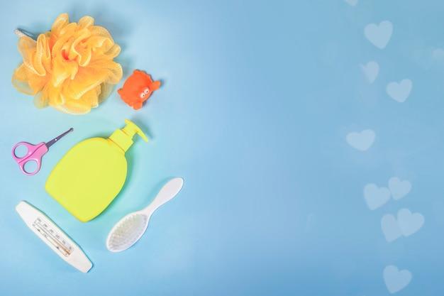 Higiena dziecięca: artykuły do kąpieli, butelka szamponu, zabawka gumowa, gąbka, grzebień, termometr, nożyczki bezpieczeństwa widok z góry, na niebieskim tle. miejsce na kopię. zestaw do higieny osobistej dla dzieci. akcesoria do kąpieli.