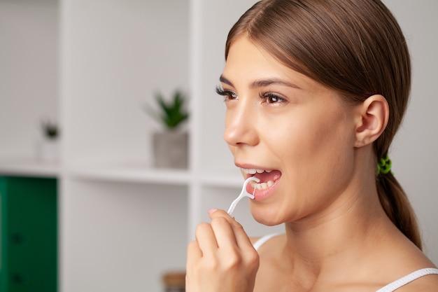 Higiena jamy ustnej i opieka zdrowotna, uśmiechnięte kobiety używają nici dentystycznej białych, zdrowych zębów.