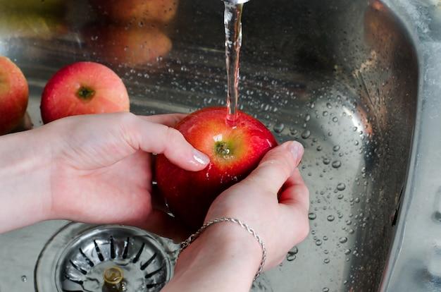 Higiena jedzenia. czerwone jabłko z plusk wody na rękach