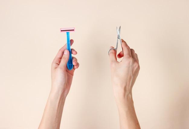 Higiena osobista, koncepcja piękna. kobiece ręce trzymając szczoteczkę do zębów i nożyczki do paznokci na beżu.