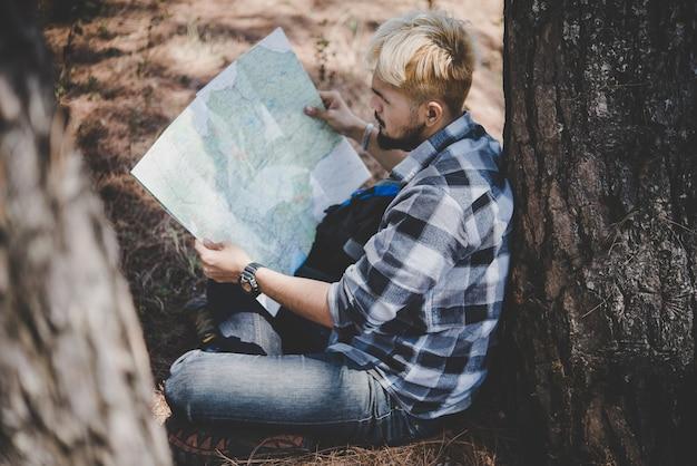 Hiker relaks na drzewie patrząc na mapę, iść przygoda w górach.