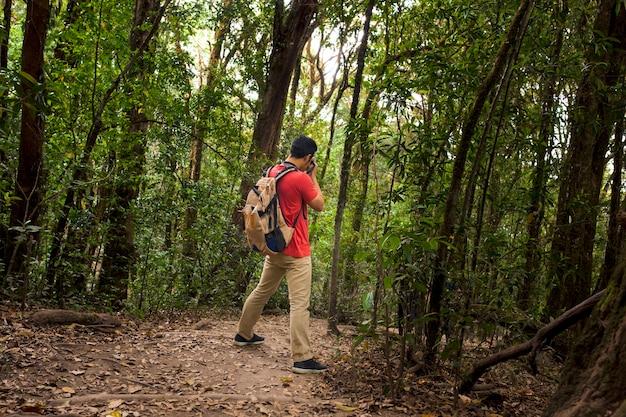 Hiker z plecakiem biorąc zdjęcie w lesie