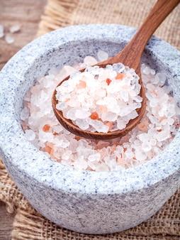 Himalajska menchii sól w moździerzu na konopianym workowym tle.