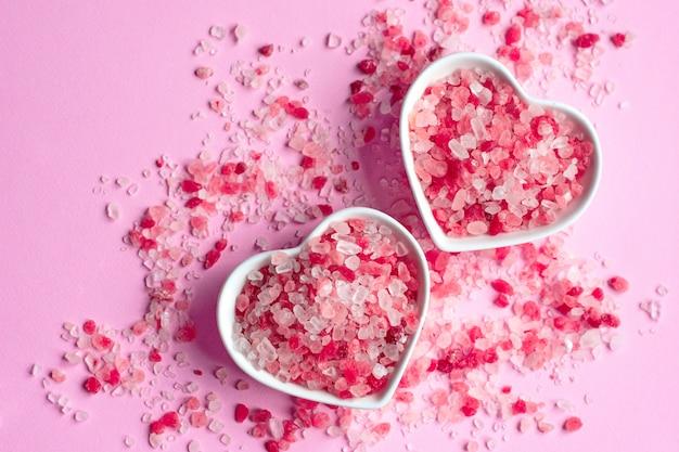 Himalajska różowa sól na różowym papierowym stole w spodku w kształcie serca