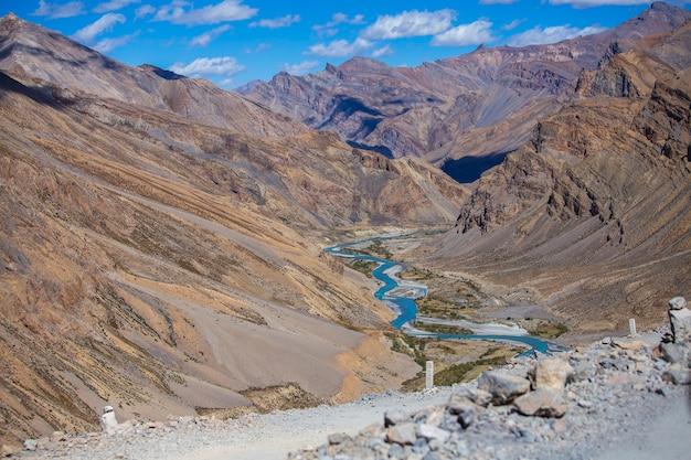 Himalajski krajobraz górski wzdłuż autostrady leh do manali w indiach. niebieska rzeka i majestatyczne góry skaliste w indyjskich himalajach, regionie ladakh, dżammu i kaszmir, indie. koncepcja przyrody i podróży