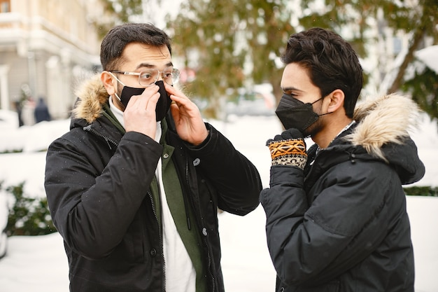 Hindusi w maskach. mężczyźni na ulicy zimą. chłopcy noszą maski.