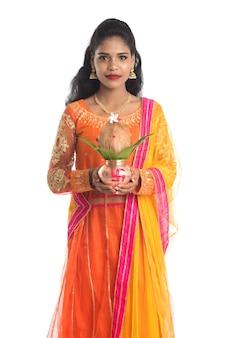 Hinduska trzymająca tradycyjną miedzianą kalaszę z kokosem i liściem mango z dekoracją kwiatową, niezbędna podczas indyjskiego festiwalu hinduistycznego i kultu