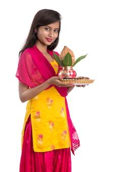 Hinduska trzymająca tradycyjną miedzianą kałaszę z pooja thali, indian festival