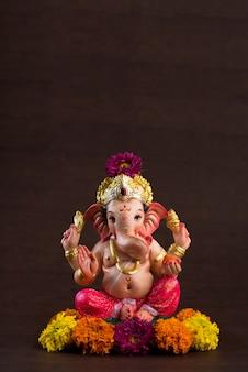 Hinduski bóg ganesha. ganesha idol na ciemnej drewnianej przestrzeni.
