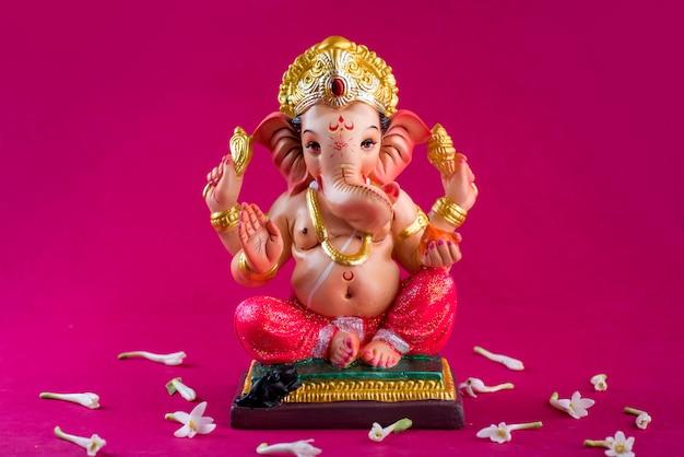 Hinduski bóg ganesha. ganesha idol na różowym stole.