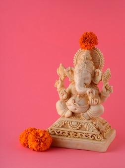 Hinduski bóg ganesha idol na różowej powierzchni