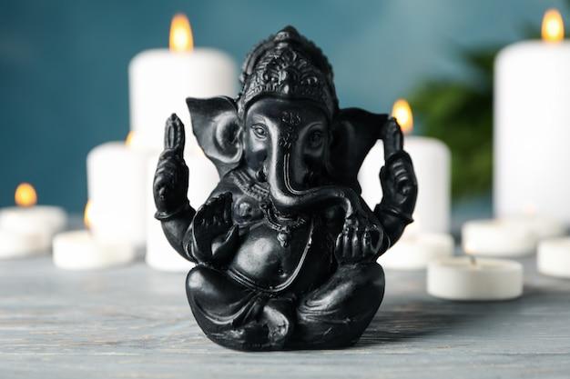 Hinduski bóg ganesha na białym drewnianym stole. świece w tle