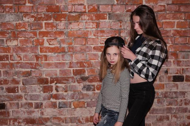 Hip hop dla nastolatków. przyjaźń stylu. nowoczesny styl życia dziewcząt, ceglany mur tło z wolną przestrzenią. miejskie życie mody, koncepcja piękna