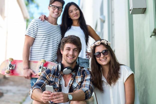 Hip przyjaciele patrząc na kamery i siedząc na schodach w mieście