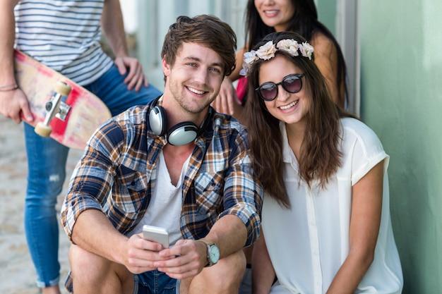 Hip przyjaciele siedzą na schodach patrząc na kamery w mieście