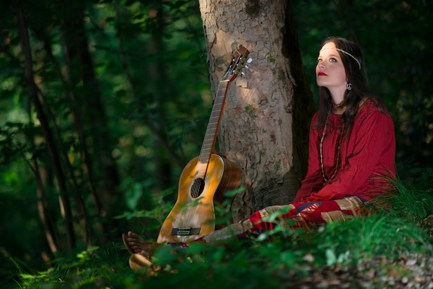 Hipis dziewczyna z gitarą w lesie
