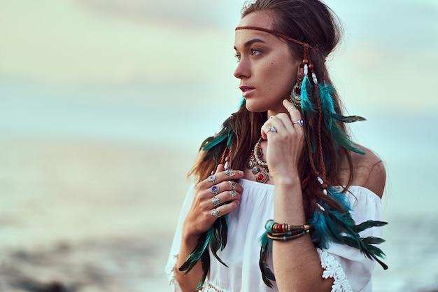 Hipis kobieta nosi niebieskie pióra, biżuterię i białą bluzkę