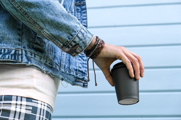 Hipis kobieta ubrana w skórzane bransoletki w stylu boho na nadgarstku i dżinsową kurtkę dżinsową trzymająca papierowy kubek kawy na wynos, uzależnienie od kofeiny, czas letni.