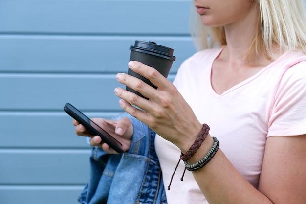 Hipis kobieta ubrana w skórzane bransoletki w stylu boho na nadgarstku trzymająca papierowy kubek z kawą na wynos i smartfon, czas letni.