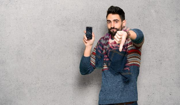 Hipisa mężczyzna z niepokojącym mienia łamającym smartphone nad textured ścianą