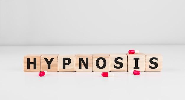 Hipnosis słowo zrobione z cegiełek z pigułkami.