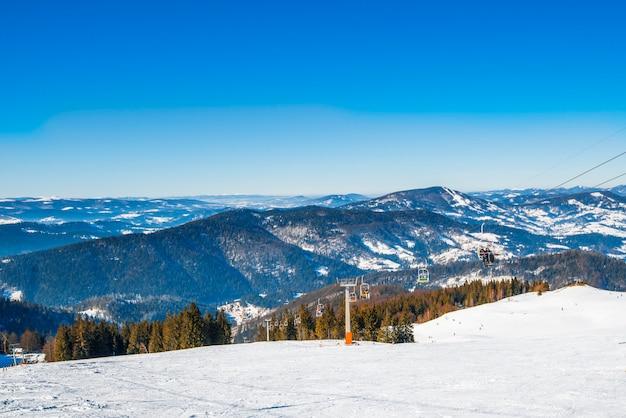 Hipnotyzująca kolejka linowa położona w malowniczym miejscu wśród gór i zaśnieżonych wzgórz oraz w mroźny zimowy wieczór na błękitnym niebie