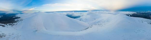 Hipnotyzująca panorama górskich klifów wzgórz pokrytych śniegiem w pochmurny zimowy dzień. pojęcie piękna przyrody i ośrodków narciarskich