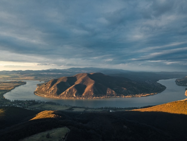 Hipnotyzująca scena rzeki między lasem a wzgórzem pod zachmurzonym niebem