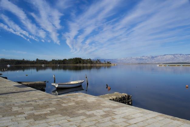 Hipnotyzujące panoramiczne ujęcie dużego jeziora pod błękitnym niebem ze strumieniami chmur