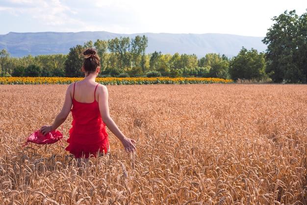 Hipnotyzujące ujęcie atrakcyjnej kobiety w czerwonej sukience, pozowanie na polu pszenicy