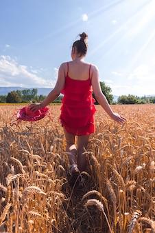 Hipnotyzujące ujęcie atrakcyjnej kobiety w czerwonej sukience pozującej do kamery na polu pszenicy