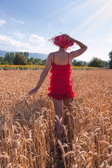 Hipnotyzujące ujęcie atrakcyjnej kobiety w czerwonej sukience pozującej na polu pszenicy