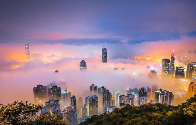 Hipnotyzujące ujęcie drapaczy chmur okrytego mgłą nocą