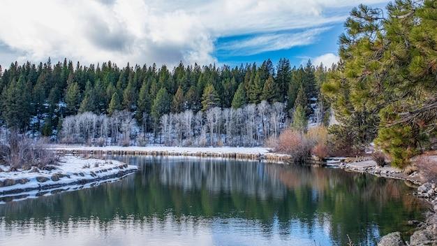 Hipnotyzujące ujęcie pięknego zaśnieżonego skalistego parku wokół jeziora