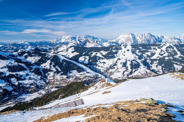 Hipnotyzujące ujęcie pokrytych śniegiem alp pod błękitnym niebem