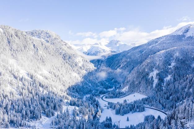 Hipnotyzujące ujęcie pokrytych śniegiem gór zimą pod błękitnym niebem