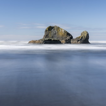 Hipnotyzujące ujęcie przedstawiające ogromną skałę z oceanem